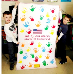 "Lucas Crutchfield (left) and Carter Early display a poster that students at South Hill Elementary School signed with handprints for the ""Hearts to Heroes"" campaign sponsored by 3WD radio station and  Mecklenburg Electric Cooperative."